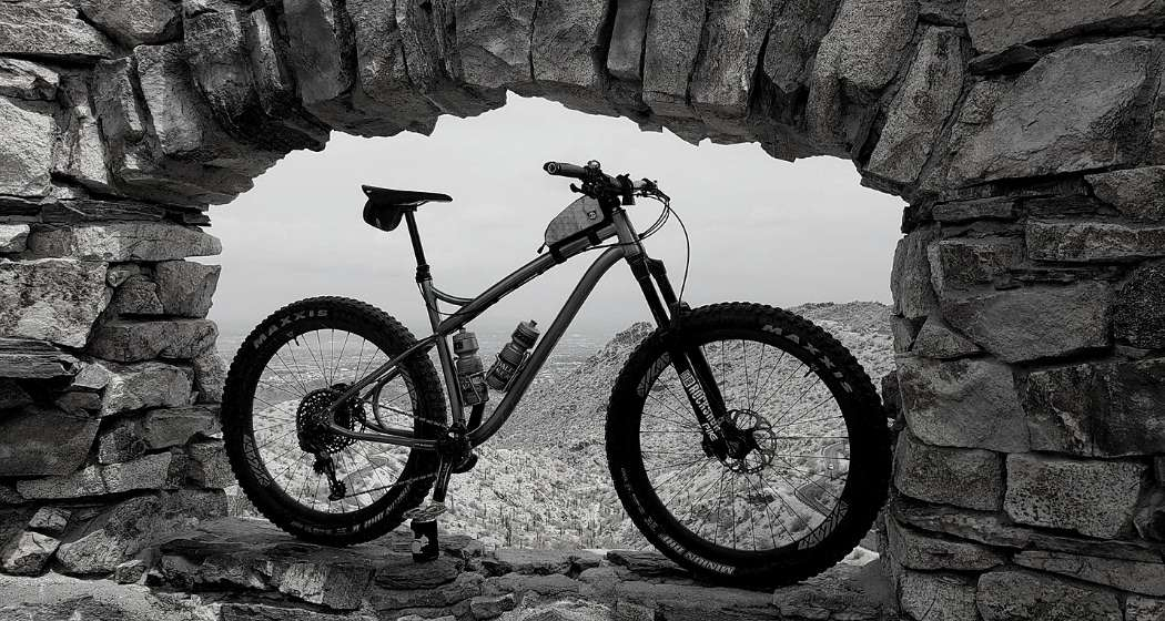 binary molotok titanium mountain bike leaning in a rock window with mountain view in the background